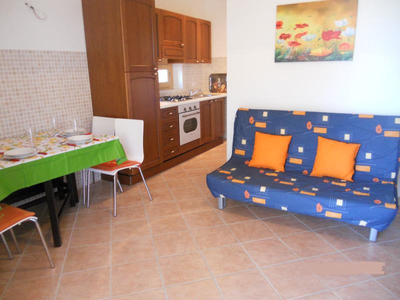 cocina con mesa de comedor para 6 personas, sala de estar con sofa-cama, salida a la terraza