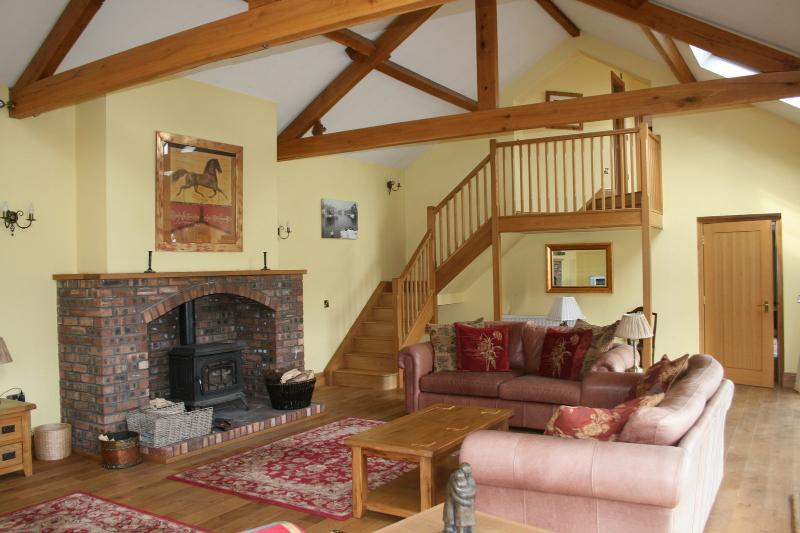 Log burner in beamed living room, with stairs up to mezzanine floor.