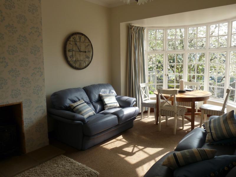 A sala de estar ensolarada com vista para o jardim do pátio