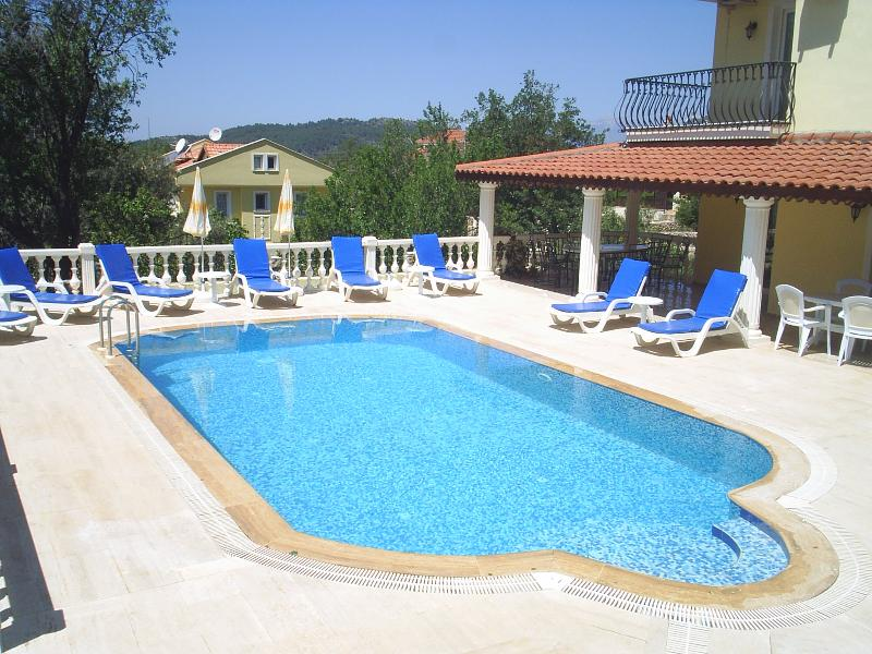 Pool, surrounded with non slip travertine tiles and plenty of sunbeds to relax on.