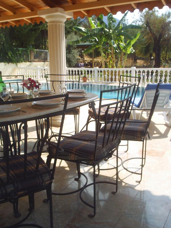Dine in style overlooking the pool and garden.