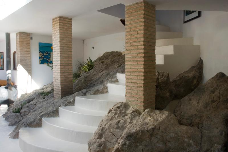 A staircase leads up through the rocks to the second bedroom