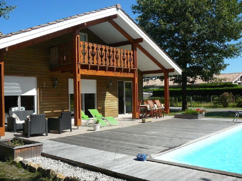 Vue d'extérieur de la maison, donnant sur la terrasse et la piscine chauffée et sécurisée.