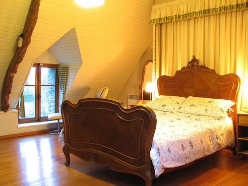 Spacious master bedroom with antique walnut French bed and dormer window views of the garden.