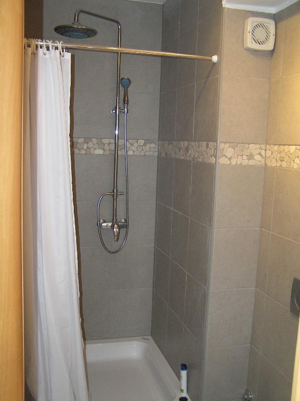 Olive Apartment shower with distinctive yet subtle beach pebble design theme