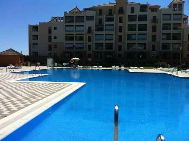 Vista general de la piscina y frontal del edificio del apartamento