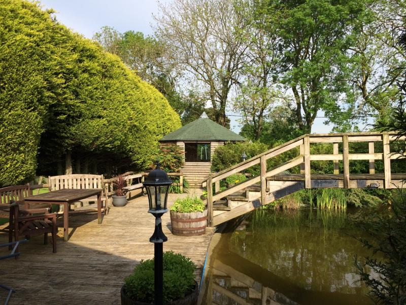 The decking surrounding the pond with various outdoor seating and tables.