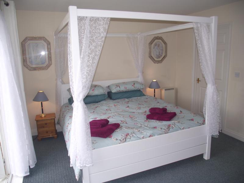Fantastic six-foot wide Superking four-poster bed in main bedroom
