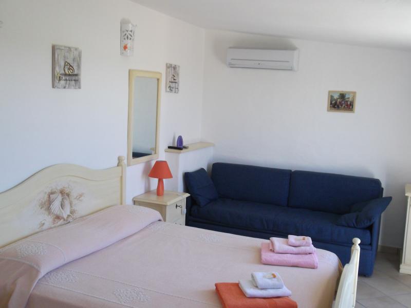 la camera arancio con il divano blu ideale per 4 persone al B&B VILLA SPRAFUNDU A LA MADDALENA