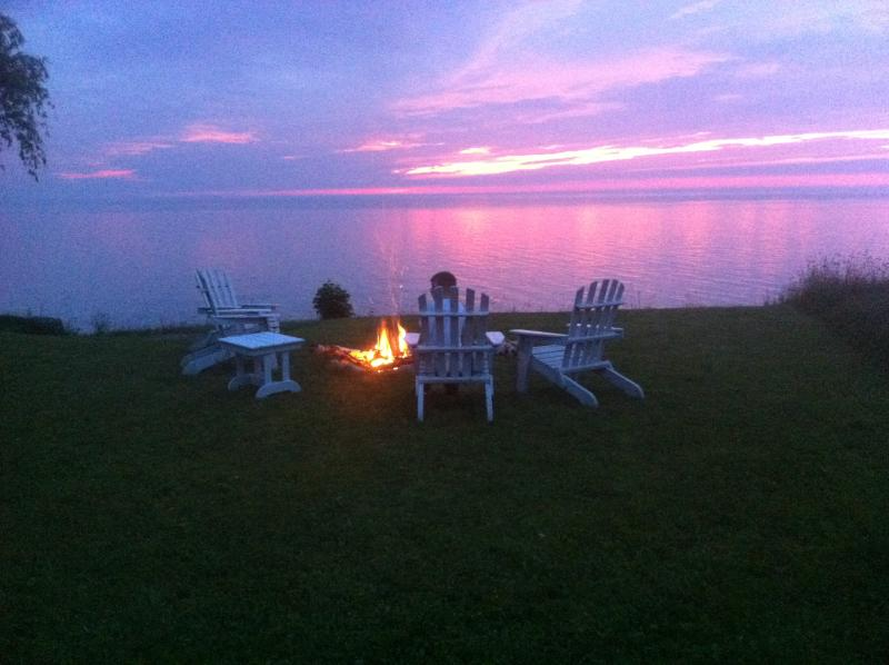 View from Lark's Cottage deck, firepit and outdoor seating at water's edge.