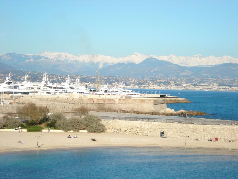 Winter view of beach, port and snow capped Alps