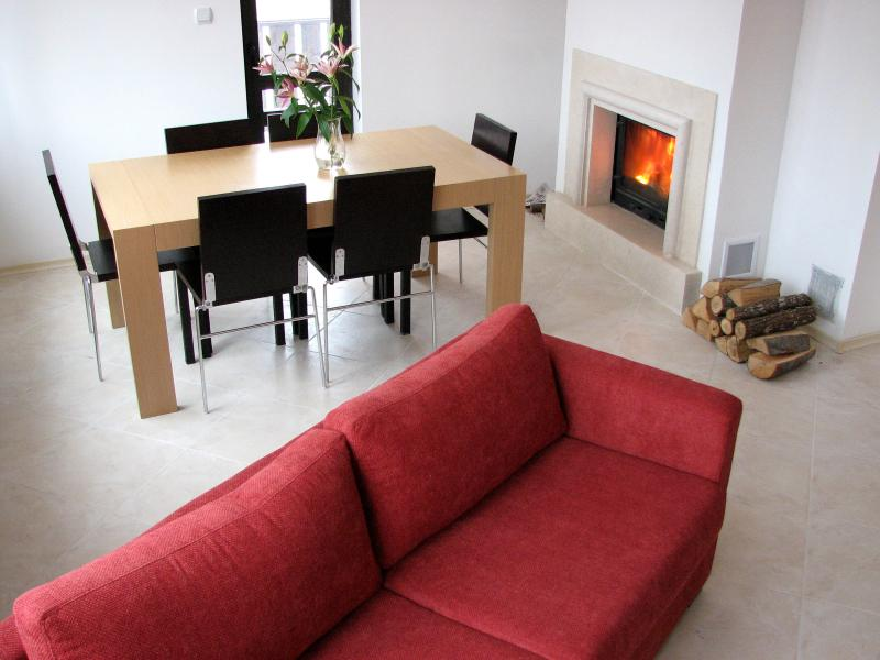 Open plan living dining area with open fire and access to balcony