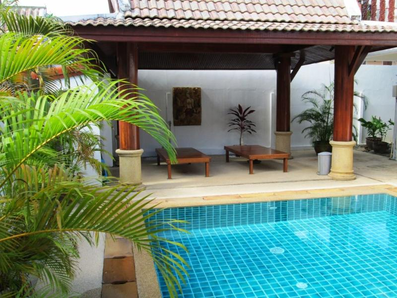 Sala next to the swimming pool with lounge chairs and BBQ