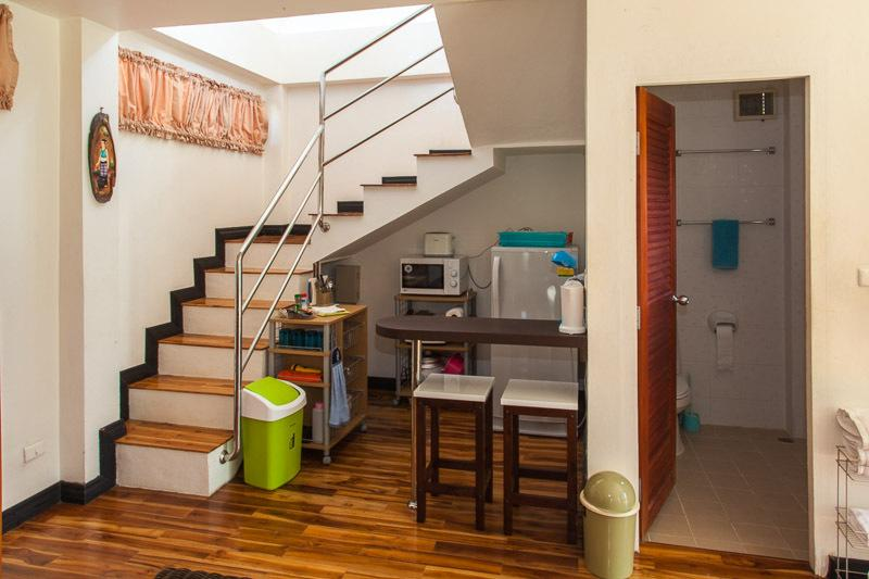 Kitchenette with refrigerator, microwave, electric appliances, stairs to BR on left; Bathroom on rt