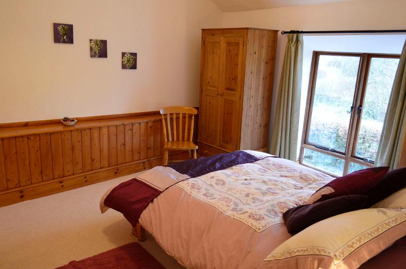 Double bed in end bedroom with view over garden and fields