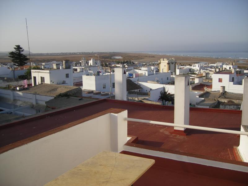 Terraza con vistas al pueblo y la playa, al atardecer