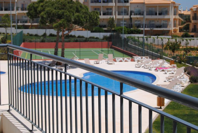 View of tennis court and swimming pool from balcony