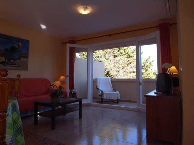 el salón con mesa central y  TV plana y armario