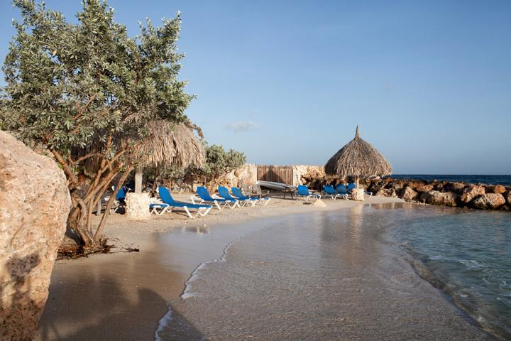 The private beach of Curaçao Ocean Resort, with beds and palapa's