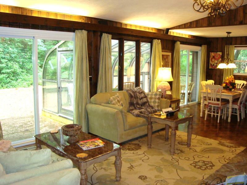 Alegre sala de estar con un montón de ventanas está abierta a comedor