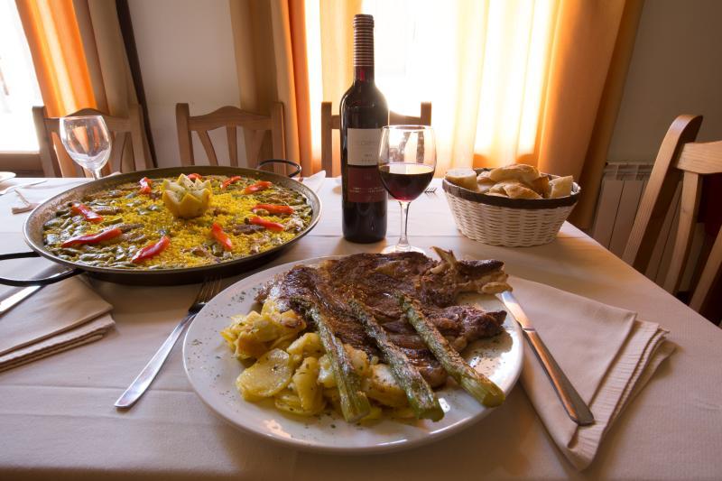 Detail restaurant Paella and veal steak with garnish