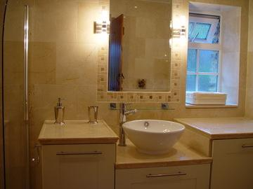 The bathroom with small plunge bath, digital shower over and vanity basin.