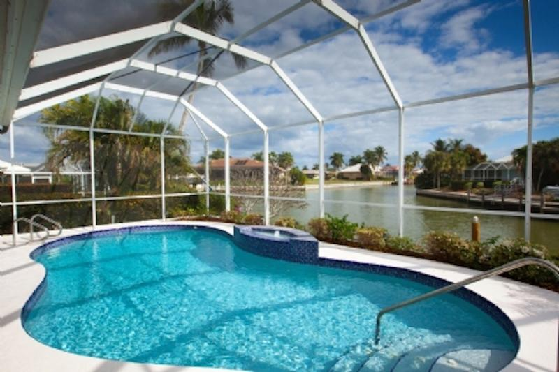 Heated pool with screened lanai and wide water view facing East-South