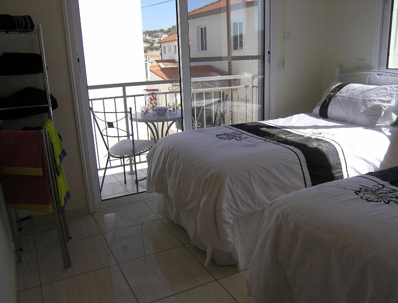 Twin bedroom with balcony & pool view..