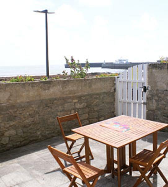 prive-terras, in de buurt, een panoramisch strand en de zee. Tuinmeubelen, parasol en twee Chileense.