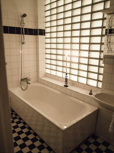 Luxurious bathroom, with underfloor heating, thick glass wall backlit with soft light during night.
