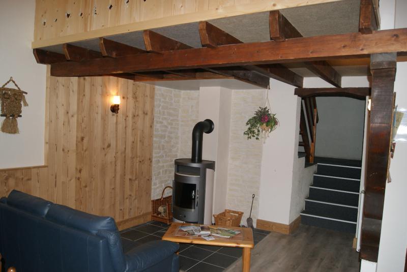 La salon, avec son poêle à bois et la mezzanine au dessus