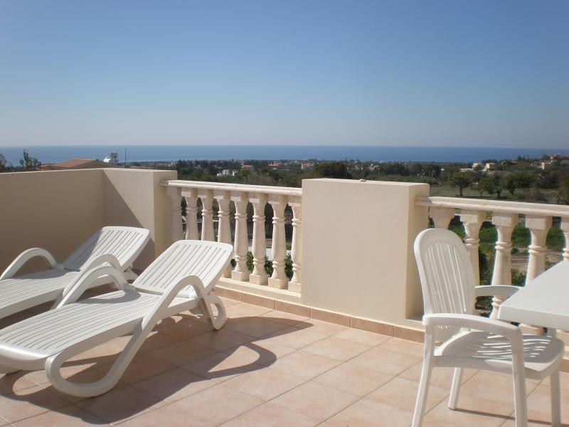 The balcony has four sun-beds, a patio table with seating for six and a parasol