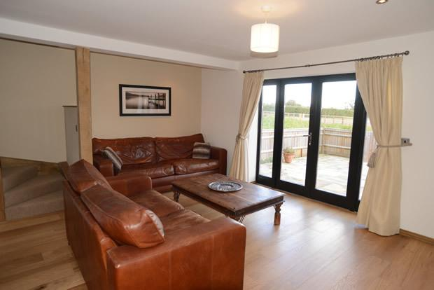 Lounge area with TV and patio doors leading to patio area