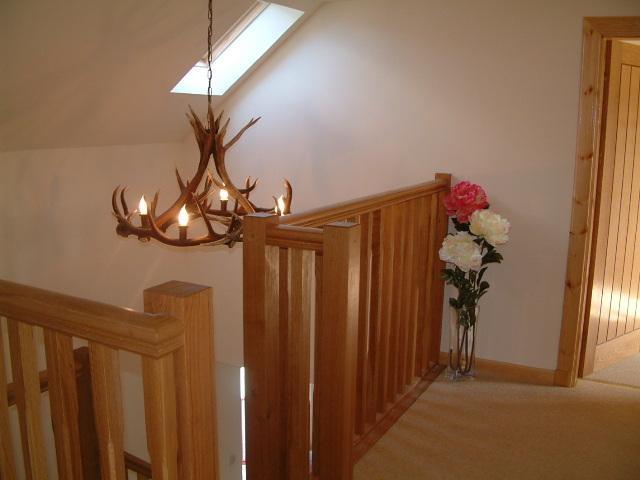 Antler chandelier over oak staircase