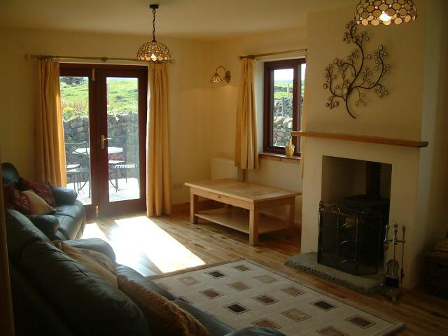 Lounge with log burner and leather settees colour tv patio doors
