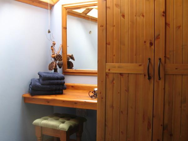 A large pine wardrobe (wooden hangers) and vanity area with hairdryer. Keep yourself looking good