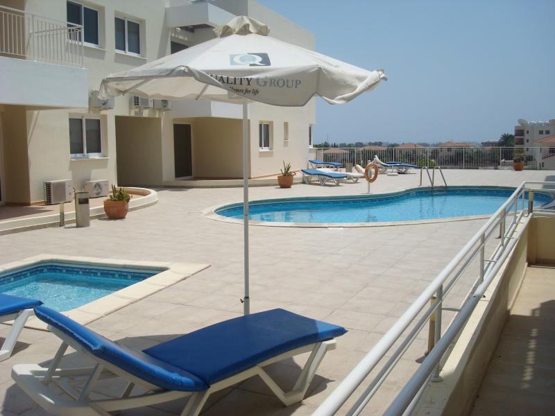 The spacious adult and children's swimming pool area with sun lounges