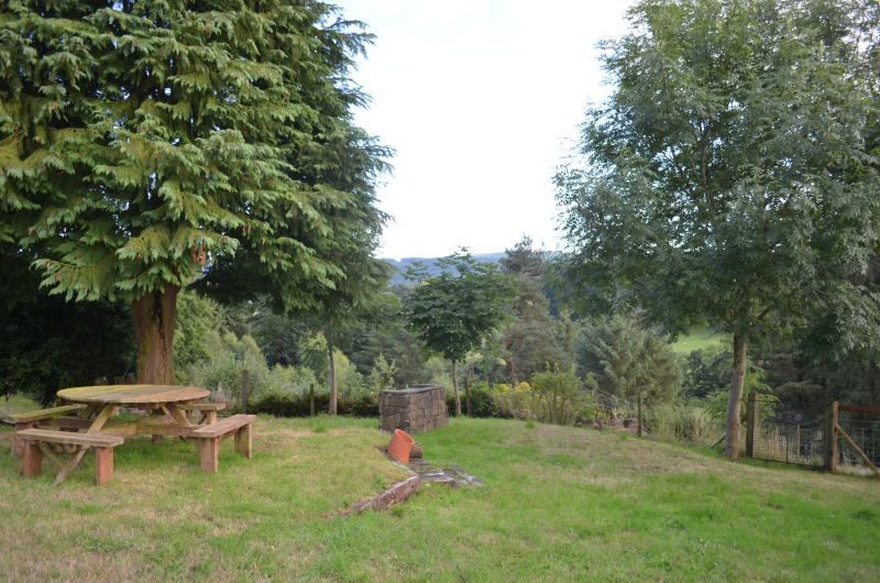 Farmhouse gardens, showing picnic table to left with BBQ just behind.