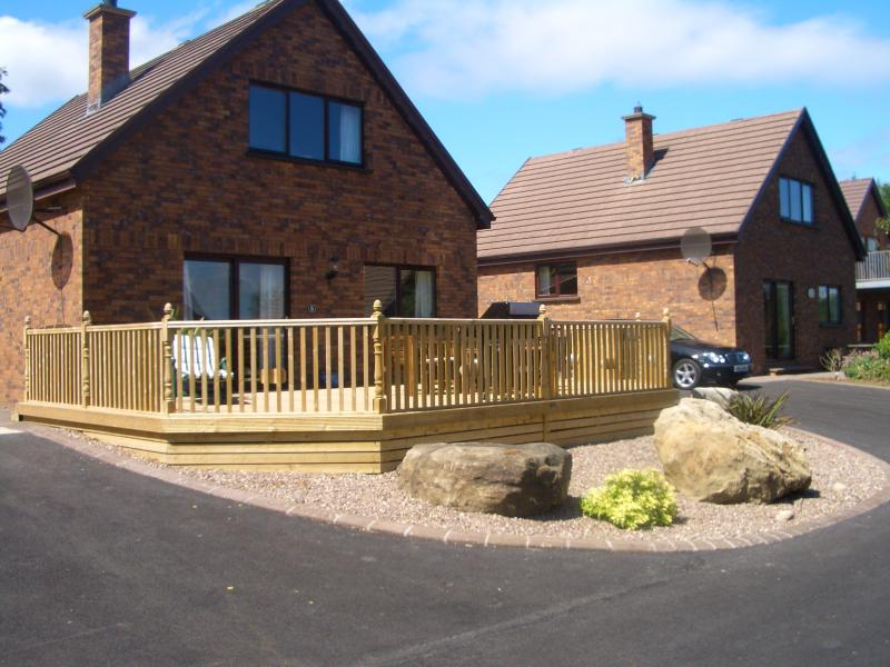 Front of house with decking area and ample parking