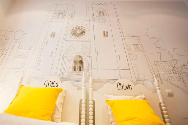 Yelow Tram suite, a two single bedroom with a large painting of the Lisbon Cathedral