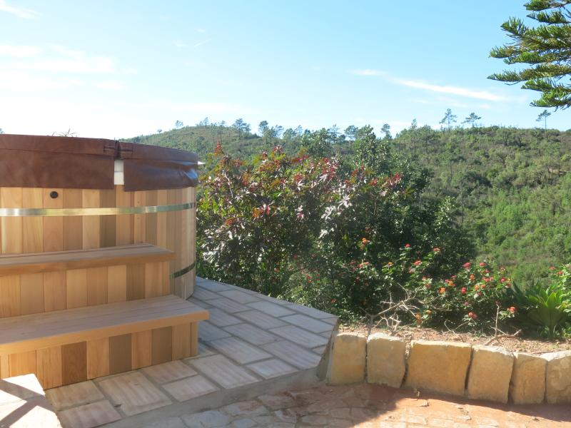 The hot tub sits a few steps from the top terrace overlooking the headland with no building in sight