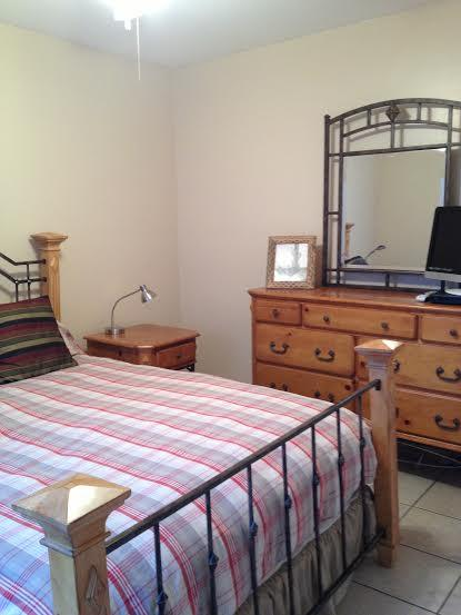 Queen bed and dresser in guest room
