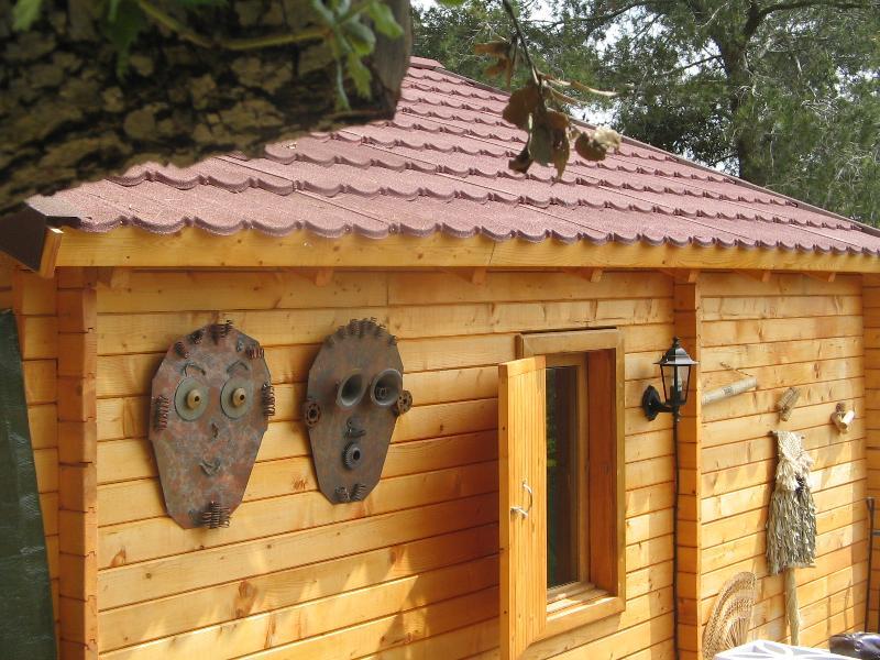 À l'extérieur de la maison de Ecoart avec deux masques artistiques