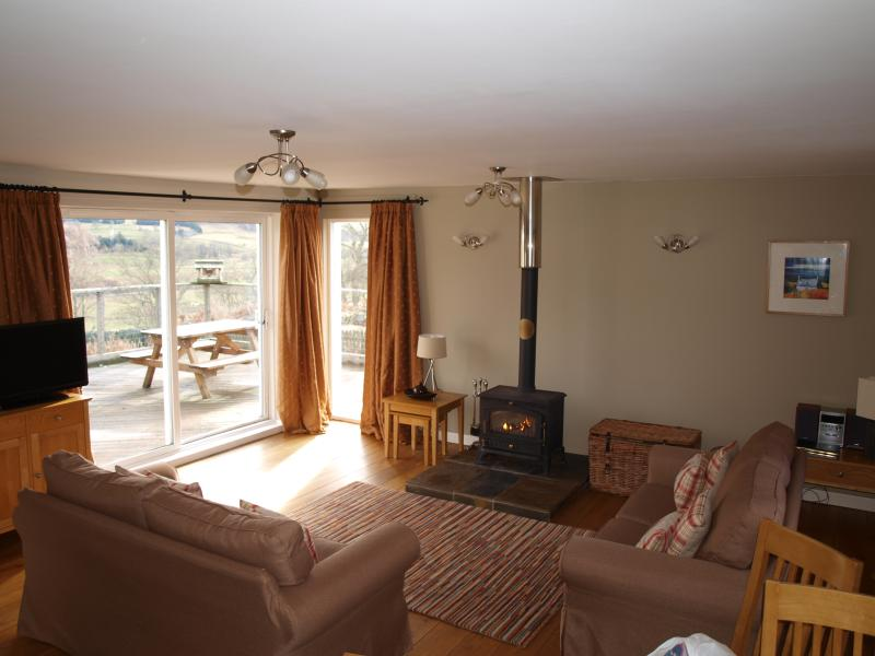 Lounge with woodburner and patio doors leading onto raised deck, garden and hot tub