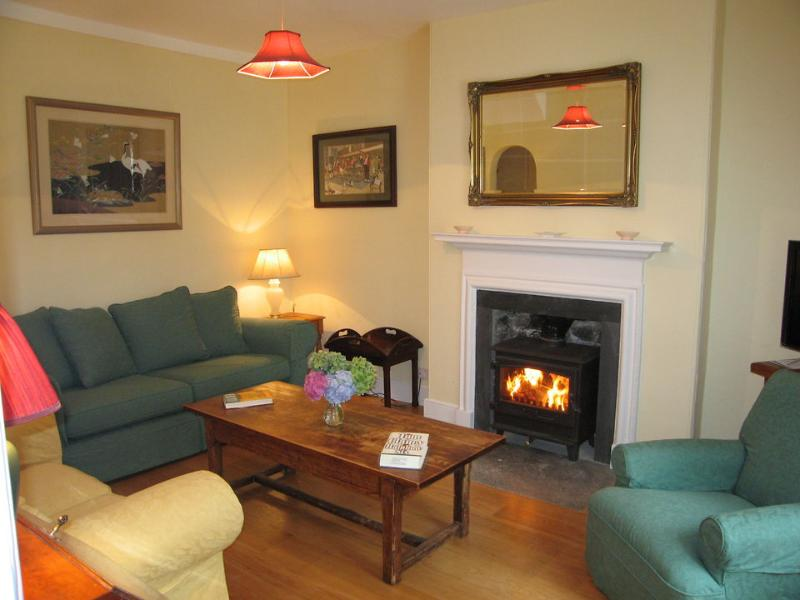 The sitting room has an open fireplace with woodburning stove