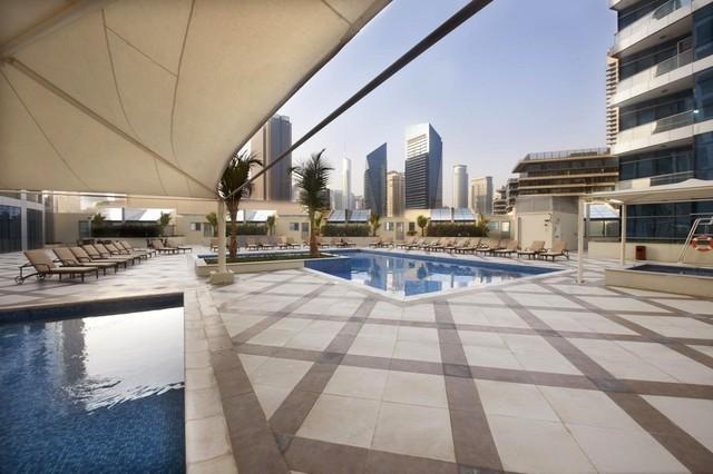 Pool deck - with adult and kids pools, jacuzzi and sunbathing deck with loungers, tables & umbrellas
