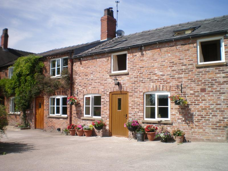 Farmhouse Cottage is adorned with honeysuckle and wisteria and adjoins the Farmhouse -on left of pic