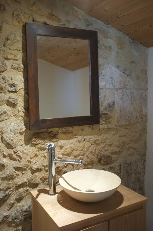 The bathroom of the family room with a stone wall and basin and a large shower