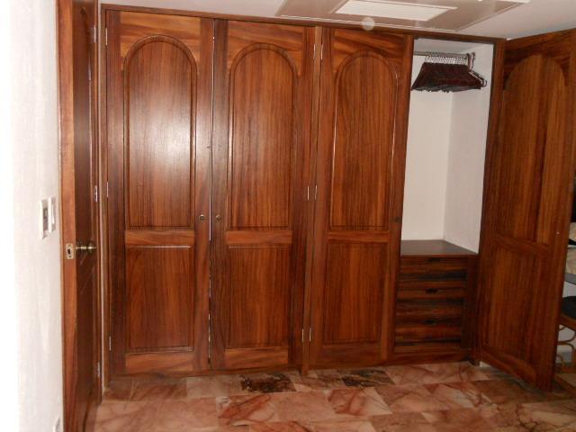 Grote kast in de slaapkamer wih laden en houten kleerhangers