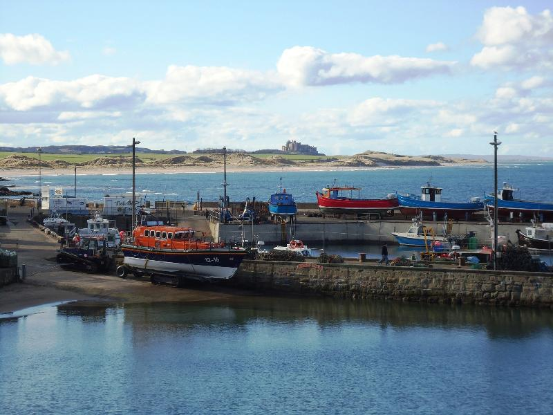 Seahouses harbour with a distant Bambugh Castle. Seahouses - 2 miles up the coast.